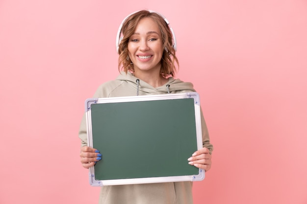 Woman holding empty chalkboard over pink background
