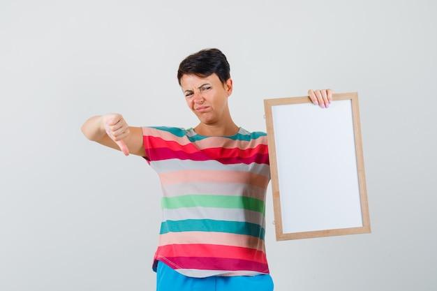 空のフレームを保持し、ストライプのtシャツ、ズボンで親指を下に示し、不満を探している女性。