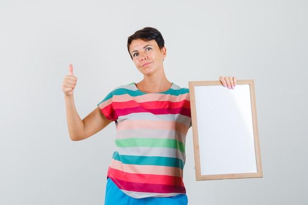 空のフレームを保持し、ストライプのtシャツ、ズボンで親指を表示し、自信を持って見える女性。
