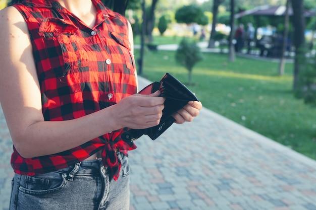 거리에서 빈 지갑을 들고 있는 여자