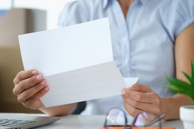 Женщина, держащая конверт с бумажным письмом или приглашением внутри, получает концепцию письменных уведомлений