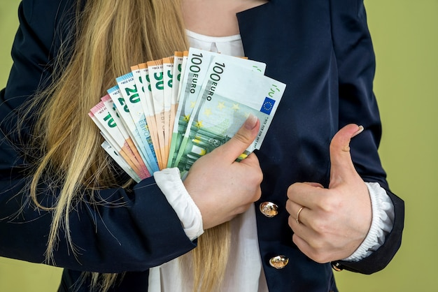 Woman holding euro banknotes isolated on green