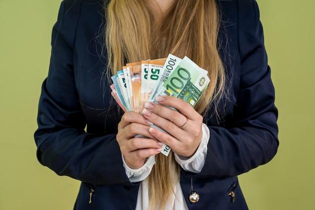 Женщина держит изолированные банкноты евро