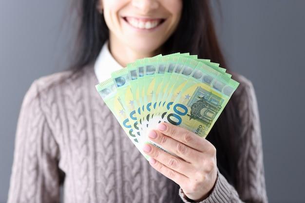 Женщина, держащая наличные евро в ее руках крупным планом. концепция успешных деловых сделок