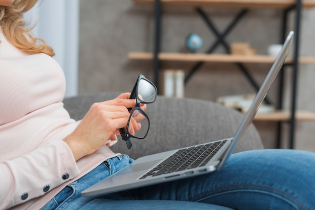 Woman holding eyeglasses in hand sitting on sofa with an open laptop on her lap