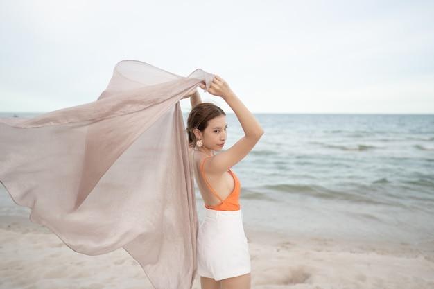 ビーチでの休日の休暇で風に生地を保持している女性。旅行と健康。