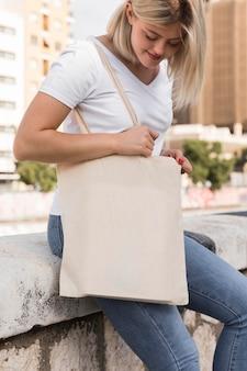 Donna che mantiene una borsa in tessuto guardando verso il basso