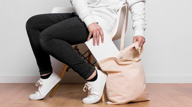 Donna che mantiene una borsa in tessuto