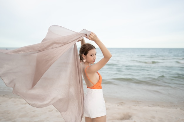 Woman holding fabric at wind in a holiday vacation at beach. travel and healthy.