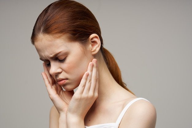 Woman holding on to face pain in teeth studio treatment