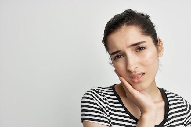 Woman holding on to face toothache health care isolated background. high quality photo