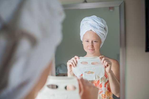 Woman holding a facial mask sheet
