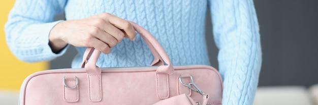 Женщина, держащая модную розовую сумку для ноутбука крупным планом, распродажа концепции аксессуаров