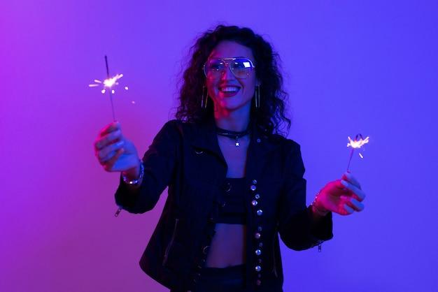 축제 불타는 향을 들고 즐거운 시간을 보내는 여자. 새해, 생일, 휴일, 이벤트, 축하, 재미.