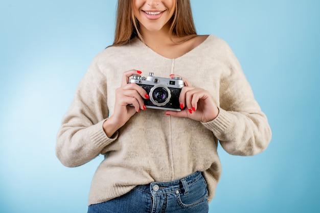 青で分離された手でフィルム写真カメラを保持している女性