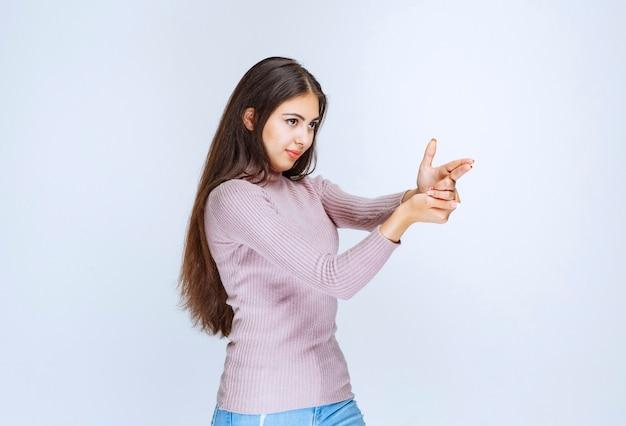 Женщина, держащая палец пистолет знак, как преступник.