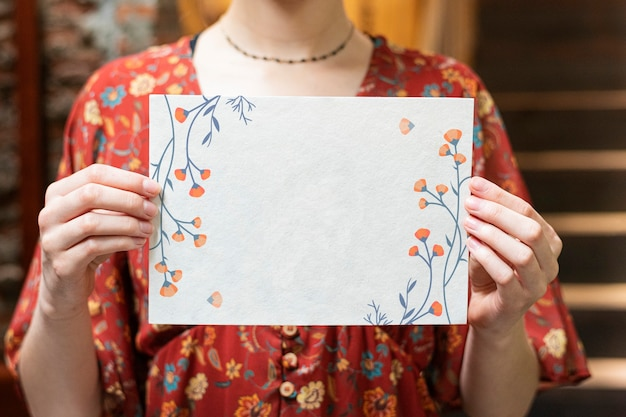 Woman holding a floral card