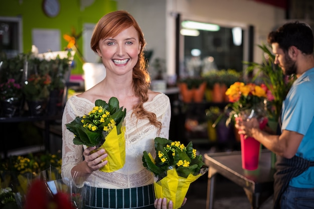 Woman holding flower bouquet while man working in the background