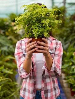 Woman holding flower pot covering head in greenhouse