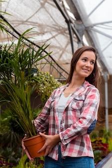 Женщина, держащая цветочный горшок в теплице, глядя