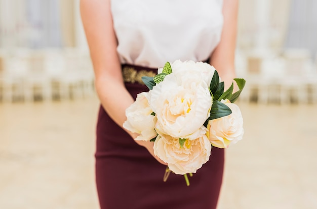 Woman holding flowers bouquet in hands