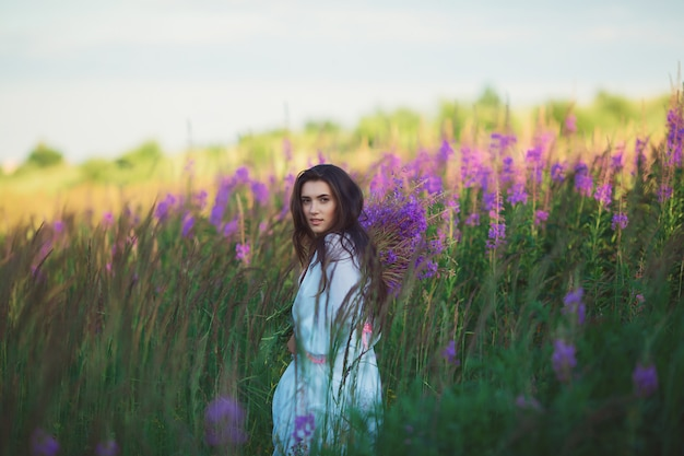 Женщина с цветами в руках, мягко улыбаясь