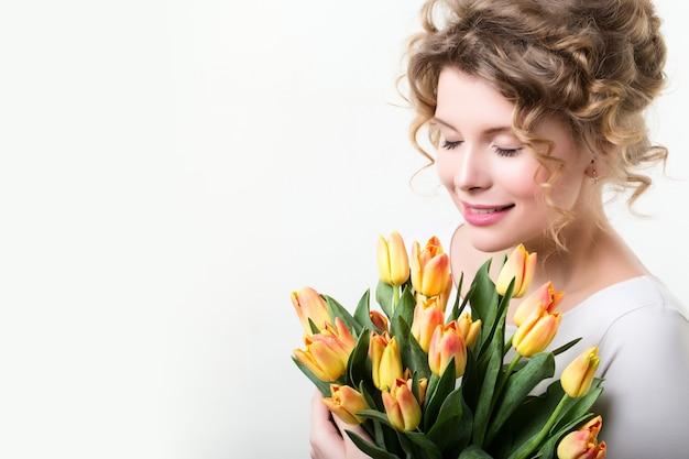 Женщина, держащая тюльпаны цветов.