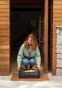 Woman holding a food basket that was delivered to her door