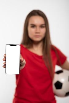 Женщина, держащая футбольный мяч и телефон
