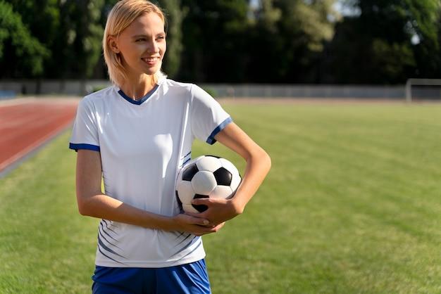 Donna che tiene un pallone da calcio sul campo