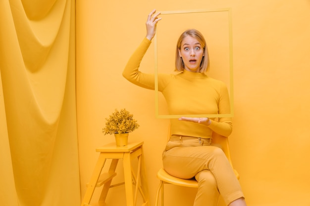 Woman holding frame around face in a yellow scene