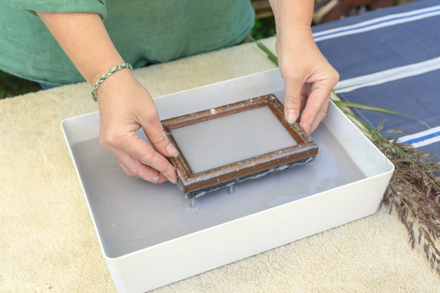 Woman holding frame for making paper sheets from waste paper pulp. selective focus. decorative and applied art. recycling concept, ecology.