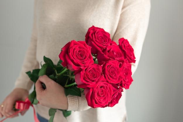 赤いバラの新鮮な花の花束を保持している女性