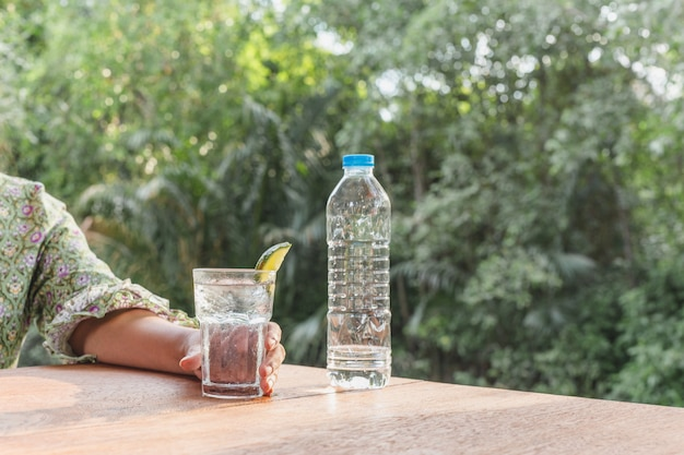 Woman holding fresh glass of water with lime detox drink.