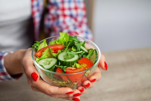 Женщина, держащая салат из свежих овощей в прозрачной тарелке