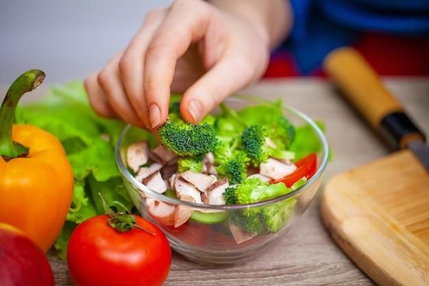 Женщина, держащая салат из свежих овощей в прозрачной пластине.