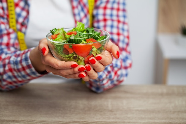 Woman holding fresh vegetable salad in a transparent plate