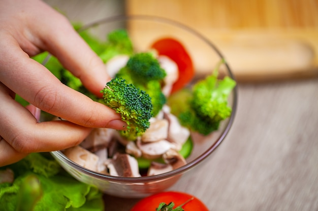 Woman holding fresh vegetable salad in transparent plate.