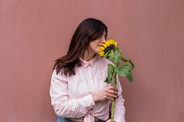 新鮮な黄色の花を持つ女性