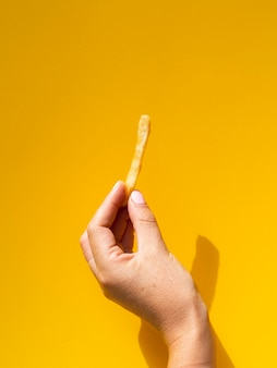 Woman holding fries in front of yellow background