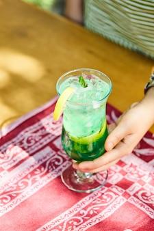 Donna che mantiene una limonata alla frutta sulla tavola di legno