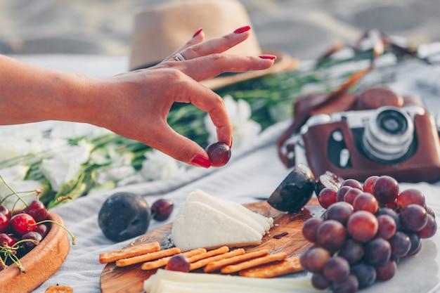 木製のまな板とカメラ、帽子、ビーチで花とチーズとフルーツのフルーツを保持している女性。