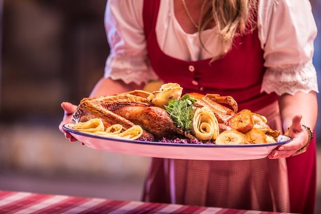 Женщина, держащая гарнированную жареную утку в пабе или ресторане.