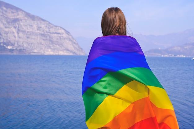 湖、屋外の山の近くのゲイの虹色の旗を保持している女性。同性カップルの幸せ、自由、愛のコンセプト。コピースペース。