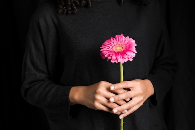 手でガーベラの花を持つ女性
