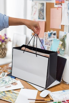 Woman holding gift bag over desk