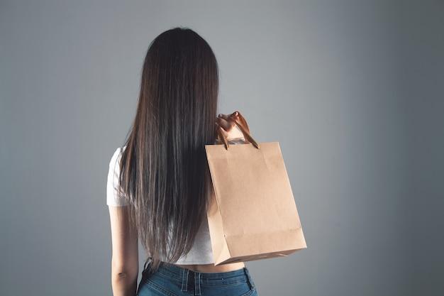 灰色の背景にギフトバッグを保持している女性