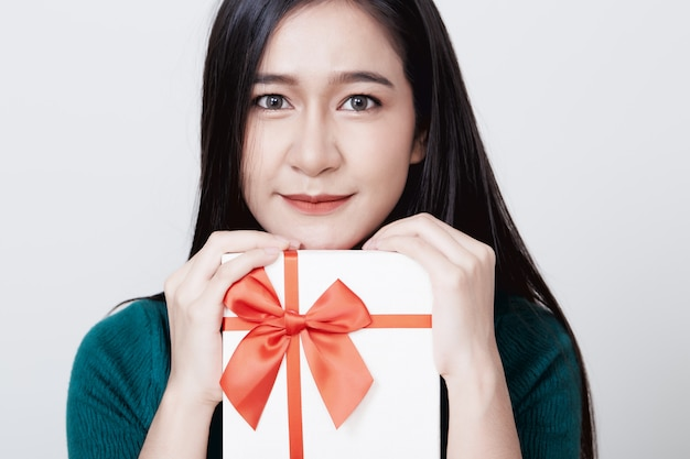 Woman holding gift box christmas on white