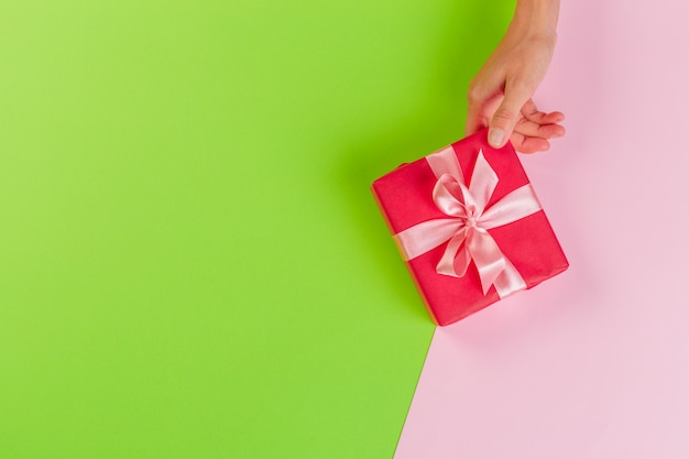 Woman holding gift box on color