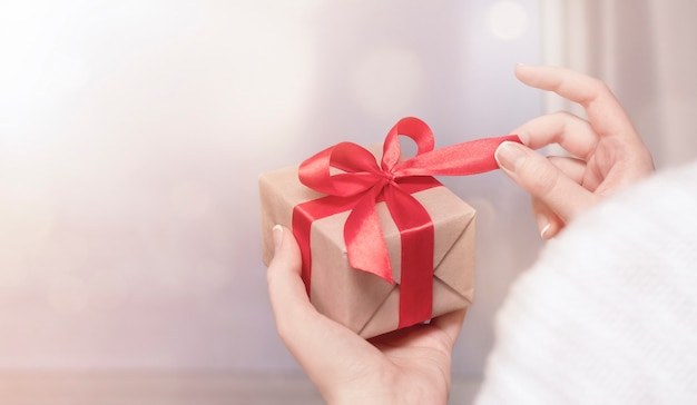 Woman holding a gift box in her hand and untie a bow